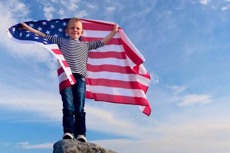 4k. Blonde boy waving national USA flag outdoors over blue sky at summer - american flag, country, patriotism, independence day 4th july 版權商用圖片