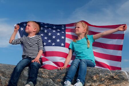 Blonde boy and girl waving national USA flag outdoors over blue sky at summer - american flag, country, patriotism, independence day 4th july