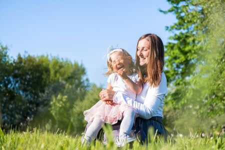 Happy mother and little daughter playing having fun outdoor in park at summer. Family lifestyle. Mom resting together on the green grass 版權商用圖片
