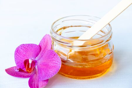 depilation and beauty concept - sugar paste or wax honey for hair removing with wooden waxing spatula sticks in jar on flower background 版權商用圖片