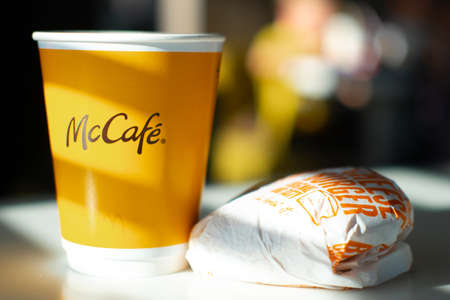 McCafe menu in McDonalds restaurant. Yellow cup of coffee and cheeseburger on table. Breackfast, time for coffee. FInland, Vantaa, 28feb2020.