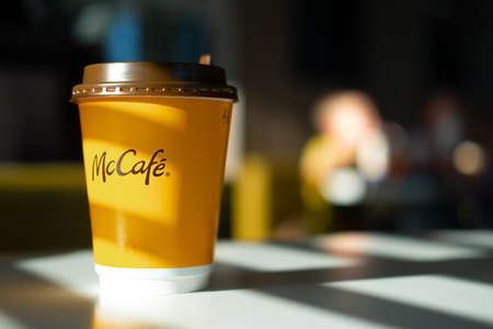 McCafe menu in McDonalds restaurant. Yellow cup of coffee on table with shadows from the sun. Breackfast, time for coffee . FInland, Vantaa, 28feb2020. 新聞圖片