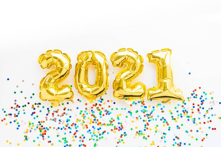 Happy New year 2021 celebration. Gold and silver foil balloons numeral 2021 and confetti on pink background. Flat lay