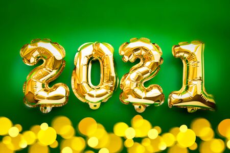 Happy New year 2021 celebration. Gold foil balloons numeral 2021 and festive bokeh lights on green background. Flat lay. 版權商用圖片