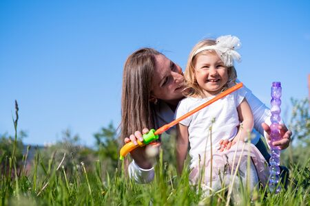 Happy mother and little daughter blow bubbles playing having fun outdoor in park at summer. Family lifestyle. Mom resting together on the green grass 版權商用圖片