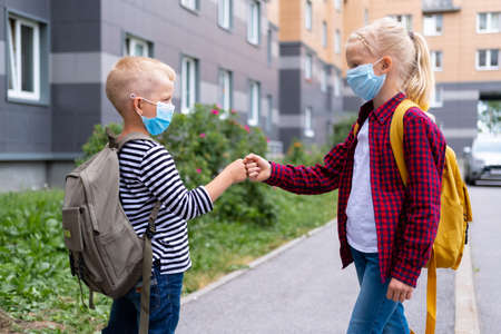 children greeting. Kids wearing mask and backpacks protect and safety coronavirus for back to school. Bou and girl going school after pandemic over