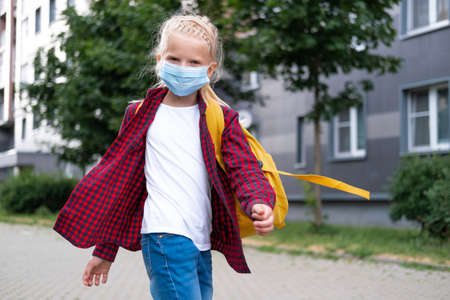 back to school. Girl wearing mask and backpacks protect and safety from coronavirus. Child going school after pandemic over. Looking at camera students are ready for new school year.