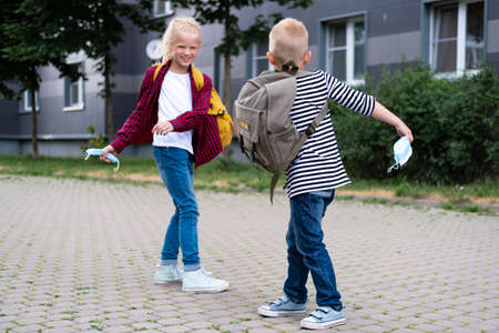 back to school. children playing on street. Kids wearing mask and backpacks protect and safety coronavirus. Boy and girl going school after pandemic over