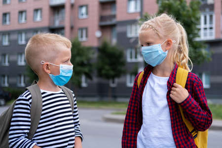 Kids wearing mask and backpacks protect and safety from coronavirus for back to school. Brother and sister going school after pandemic over. students are ready for new school year.