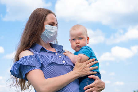 Serios baby on mother hand. Mom in protective medical mask holds her little sonover blue sky at summer. End of coronavirus.