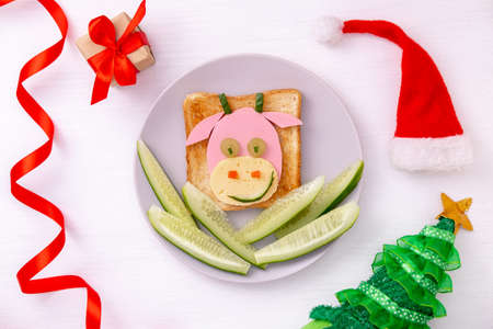 Funny sandwich with edible symbol of 2021 bull cow made from toast bread, sausage and cheese, cucumber Breakfast idea for kids. New Year Christmas food top view . holiday, celebration, food art.