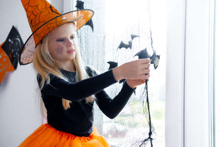 Happy girl in witch costume preparing for Halloween Decorating window in room by black bats. Imagens