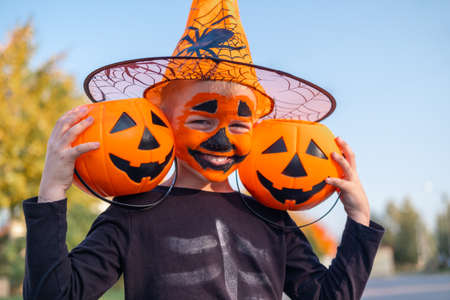 Halloween kids. Laughing boy with pumpkin face mask in witch hat with two candy buckets sitting on street.