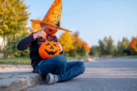 Halloween kids. boy with pumpkin face mask in witch costume hat eating candy from buckets sitting on street.