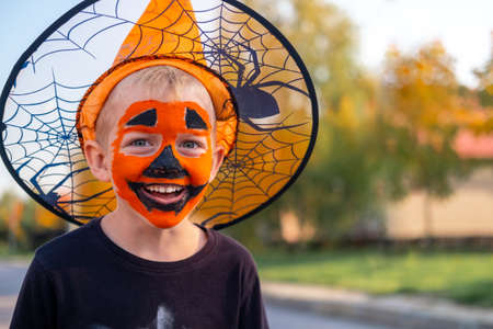 Halloween kids. Portrait Laughing boy with pumpkin face mask in witch costume hat with candy bucket on street.