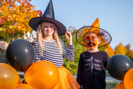 Halloween kids. Brother and sister in carnival costumes outdoors. Boy and girl in witch hat with pumpkin candy buckets. Funny kids with orange and black balloons Stock fotó