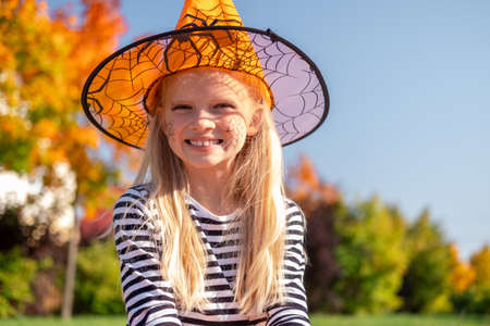 Halloween kids. Portrait smiling girl in witch hat with pumpkin candy bucket. Funny kids in carnival costumes outdoors. Stock fotó