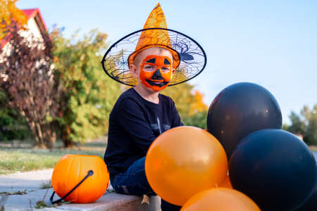 Halloween kids. Portrait smiling boy in witch hat with orange and black balloons. Funny kids in carnival costumes outdoors. Stock fotó