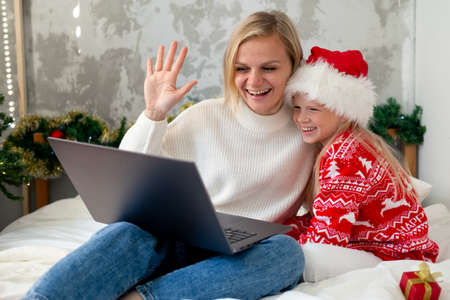 Christmas online family congratulations. Smiling european blonde mother and daughter using mobile tablet for video call friends and parents.