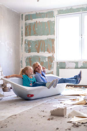 Renovation home. Mother and daughter sitting in bathtub in the middle of the room planning new interior. Empty walls, repairs house with their own hands.