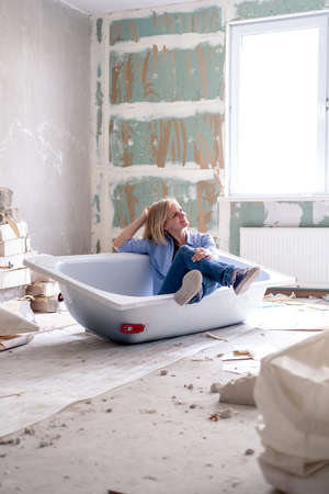 Renovation apartment. Creative story young happy woman sits in bathtub in the middle of the room. Empty walls, repairs house with their own hands. Фото со стока