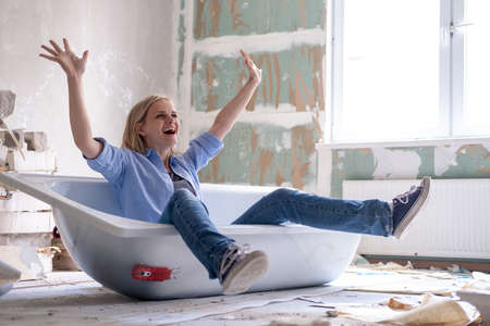 Renovation home. Excited woman sits in bathtub in the middle of the room raising arms. Empty walls, repairs house with their own hands.