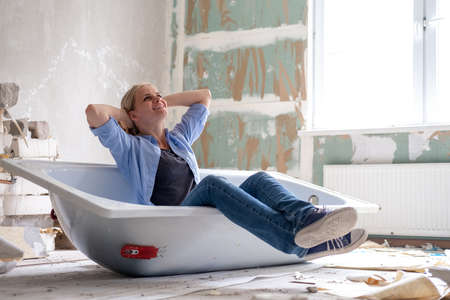Renovation apartment. Creative story young dreaming plan woman sits in bathtub in the middle of the room. Empty walls, repairs house with their own hands.