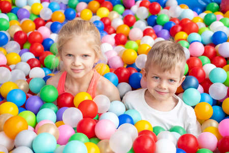 Portrait close up Smiling blonde little boy and girl lying on multi colored plastic balls in big dry paddling pool in playing centre. Having fun in playroom Leisure Activity. Фото со стока