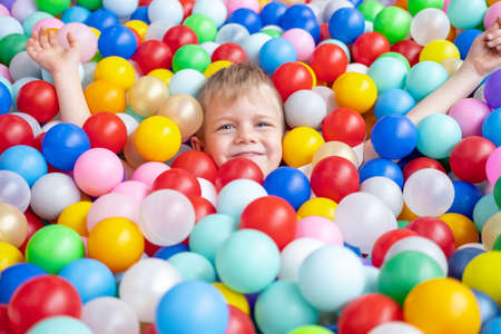 Blonde little boy lying on multi coloured plastic balls in big dry paddling pool in playing centre. Smiling at camera. Portrait close up. Having fun in playroom. Leisure Activity.