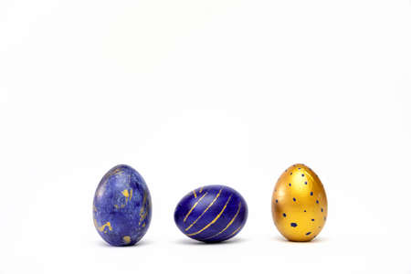 Three easter eggs trendy colored classic blue, white and golden decorated on white table. Happy Easter card with copy space for text. Minimal style.