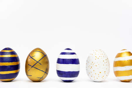 Five easter eggs trendy colored classic blue, white and golden decorated on white table. Happy Easter card with copy space for text. Minimal style. Фото со стока
