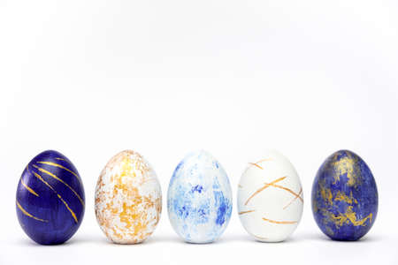 Happy Easter. Five easter eggs trendy colored classic blue, white and golden on blue. Minimal style, top view, flatlay, copy space for text. Фото со стока