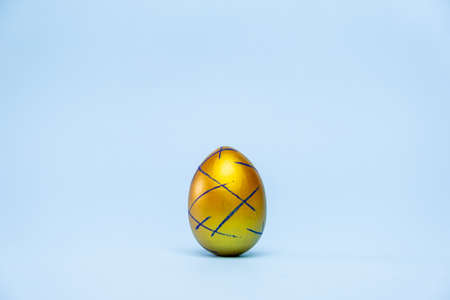 Happy Easter. One easter egg trendy colored classic blue, white and golden on blue background. Copy space. Minimal style Фото со стока