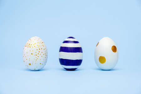 Three easter trendy colored classic blue and golden decorated eggs striped pattern on blue. Happy Easter card with copy space for text. Minimal style.