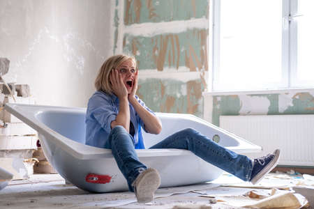 Renovation home. Excited shocked surprised woman sits in bathtub in the middle of the room. Empty walls, repairs house with their own hands. Фото со стока