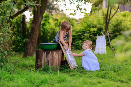 washboard: little helper girls washes white dress in a basin outdoors using the washboard outdoors