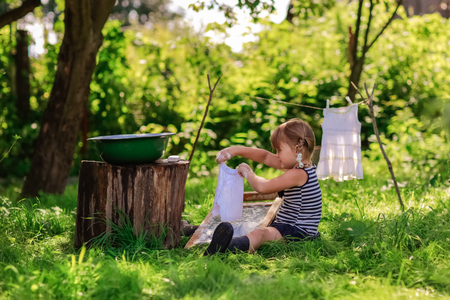 washboard: little helper girl washes white dress in a basin outdoors using the washboard outdoors