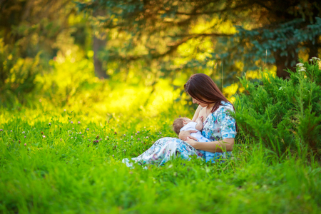 Mom feeds the baby, breastfeeding, summer photos outdoor, infant feeding Stock Photo