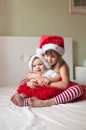 striped pajamas: Children in pajamas and Christmas caps playing on the bed, the girls,  New Year
