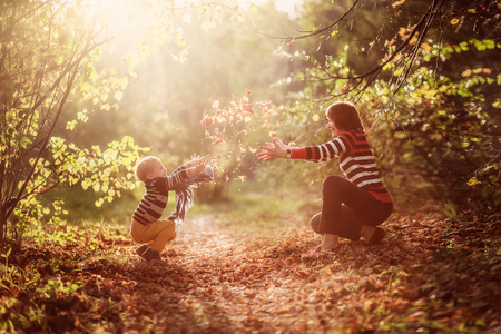 family with two children: autumn baby boy and his mother under a tree throwing yellow leaves