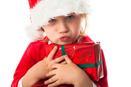 greedy: greedy, harmful funny child girl in Santa red hat holding Christmas gifts in hands. Christmas concept. play with gift