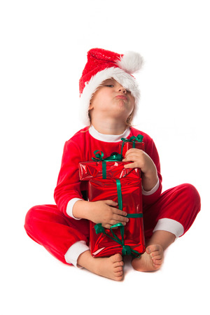 harmful: greedy, harmful funny child girl in Santa red hat holding Christmas gifts in hands. Christmas concept. play with gift