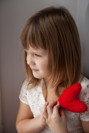 timidity: girl holding a red knit heart and waits for Valentines Day Concept, anticipation, love