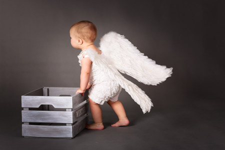 Baby angel dragging a box with the word winter, playing with the box, runs the winter