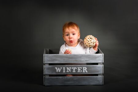 surprised kid: Surprised kid play in the gray box of winter, on a gray background