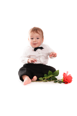 beautiful little boys: baby boy gentleman suit and tie butterfly on a white background with a rose, the concept of Valentines Day
