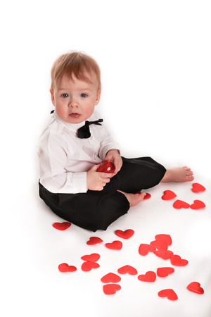 beautiful little boys: baby boy gentleman suit and tie butterfly on a white background, heartthrob plays with hearts concept valentines day