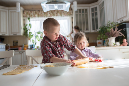 siblings: brother and sister siblings children preparing cookies in the kitchen Stock Photo