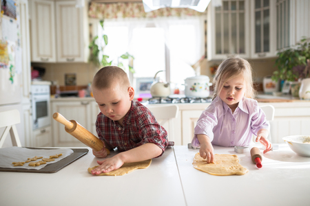 mess: brother and sister siblings children preparing cookies in the kitchen Stock Photo