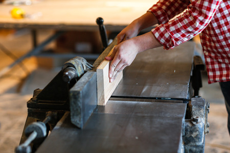 scobs: Carpenter working with big electric planer on wooden plank works at the planer Stock Photo